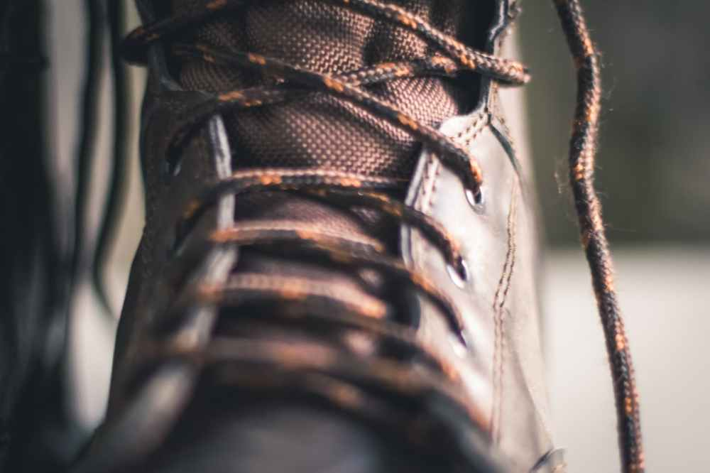 closeup photo of brown lace up boot